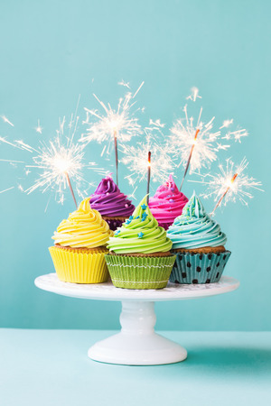 pastel de cumplea�os: Colorido cupcakes decorados con luces de bengala Foto de archivo