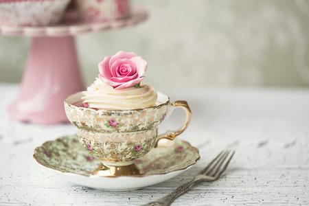 vintage: Rosa do cupcake em uma xícara de chá do vintage