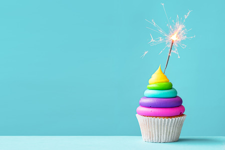 Brightly colored cupcake decorated with a sparkler