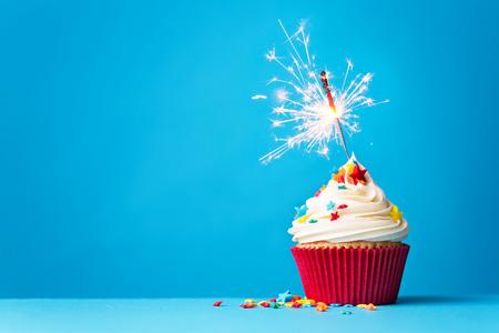 kerze: Cupcake mit Wunderkerze vor einem blauen Hintergrund Lizenzfreie Bilder