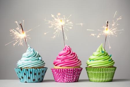 torta candeline: Fila di tre cupcakes con stelle filanti Archivio Fotografico