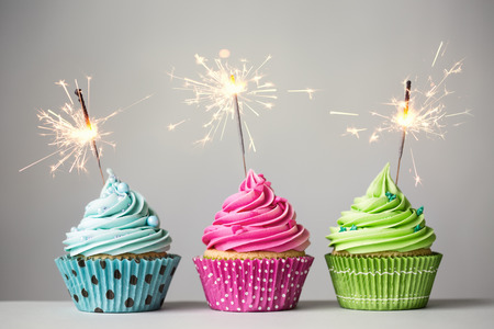 blue grey: Row of three cupcakes with sparklers Stock Photo