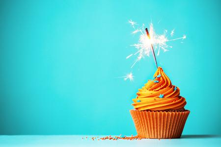 torta candeline: Cupcake arancione con sparkler e copia spazio a lato Archivio Fotografico