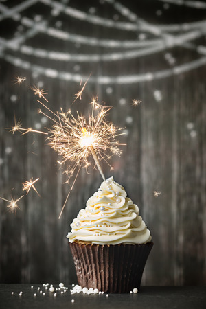gateau anniversaire: Cupcake avec sparkler contre un fond de bois