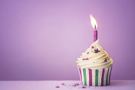 first birthday: Purple birthday cupcake with copy space to side
