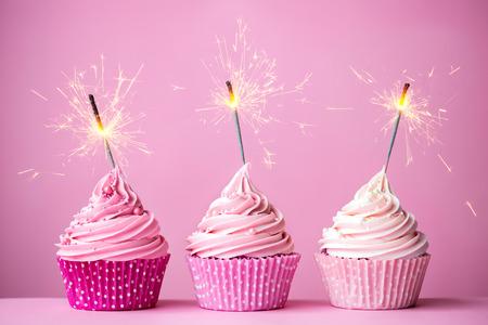 ピンクのフロスティングと花火 3 つのカップケーキ 写真素材