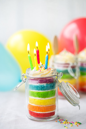layer cake: Rainbow layer cake in a jar with birthday candles