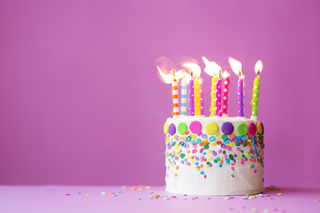 velas de cumpleaños: Torta de cumpleaños en un fondo de color rosa Foto de archivo