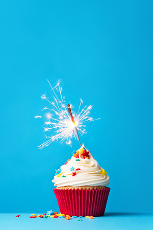 first birthday: Cupcake with sparkler against a blue background