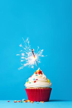 pastel cumpleaños: Magdalena con la bengala contra un fondo azul