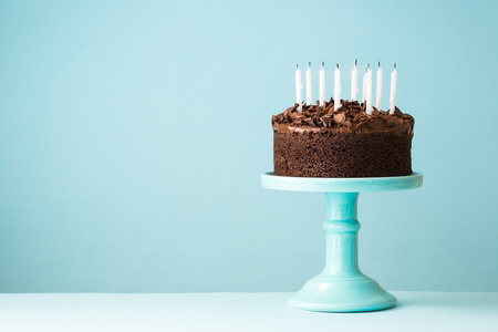 pastel de chocolate: Pastel de cumpleaños de chocolate con velas sopladas hacia fuera