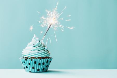 празднование: Кекс с бенгальским огнем на синем Фото со стока