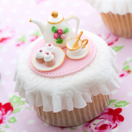 Cupcake decorated with mini sugar-paste tea party Stock Photo