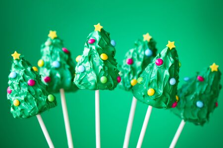 pops: Christmas tree cake pops against a green background Stock Photo
