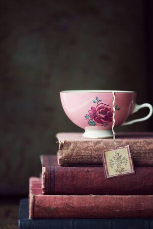 taza de té: taza de té de cosecha en la pila de libros antiguos