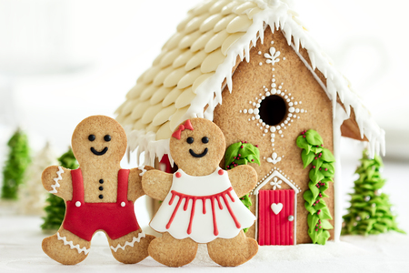 Gingerbread house with gingerbread couple in front Foto de archivo