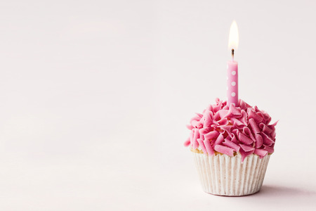 Cupcake decorated with pink chocolate curls and a single candle