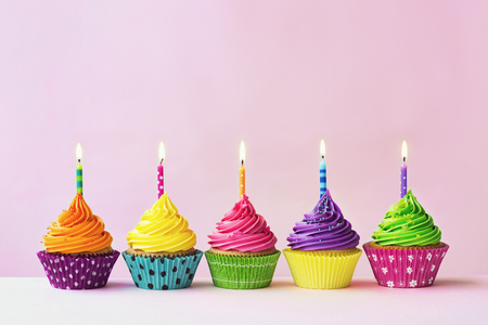 Row of colorful birthday cupcakes