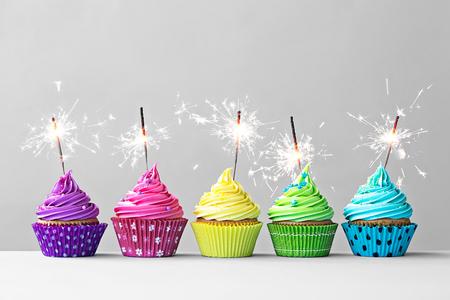 gateau anniversaire: Rangée de petits gâteaux colorés avec des cierges magiques Banque d'images