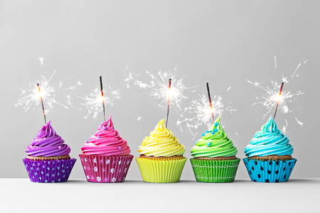 cakes background: Row of colorful cupcakes with sparklers Stock Photo