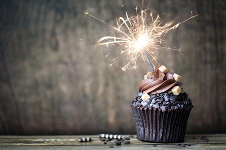 torta compleanno: Cupcake al cioccolato con un sparkler Archivio Fotografico