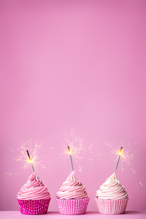 Pink cupcakes with sparklers and copy space above