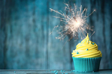 Cupcake with yellow buttercream and a sparkler Imagens - 53446814