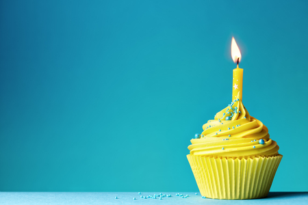 Yellow birthday cupcake on blue
