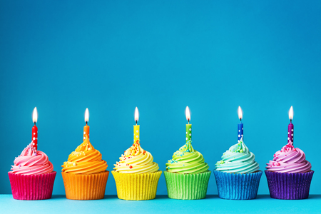 velas de cumpleaños: magdalenas del cumpleaños en colores del arco iris