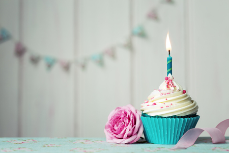Cupcake with single candle and pink rose Standard-Bild