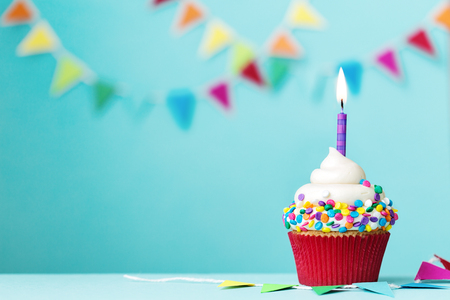 Colorful cupcake with single birthday candle Imagens - 57319465