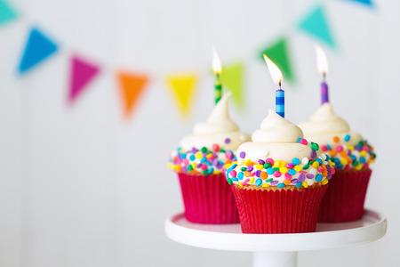 magdalenas del cumpleaños de colores sobre un soporte de la torta Foto de archivo
