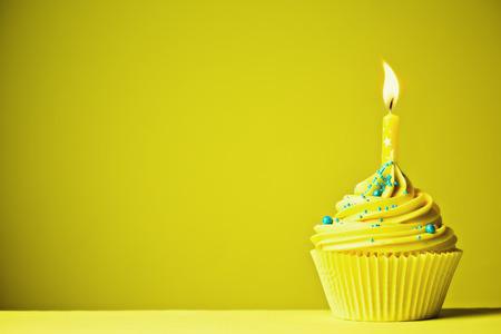 単一の黄色のキャンドルで飾られたケーキ