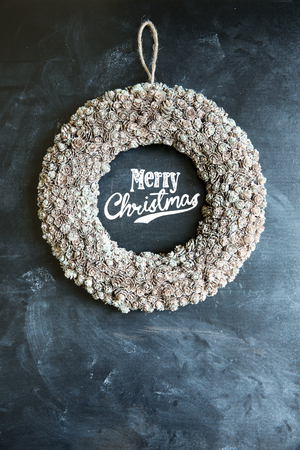 Christmas wreath with Merry Christmas written on chalk board