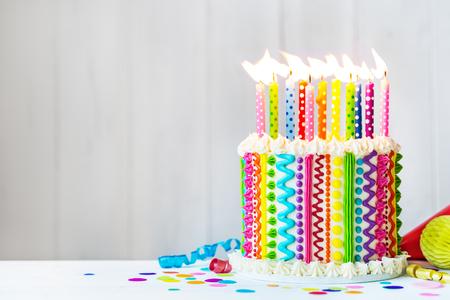 Regenboogkoek met kleurrijke kaarsen