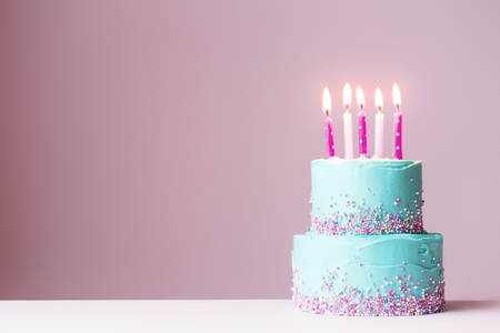Tiered birthday cake with pink candles Foto de archivo