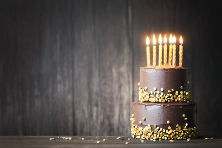 Chocolate birthday cake with gold candles
