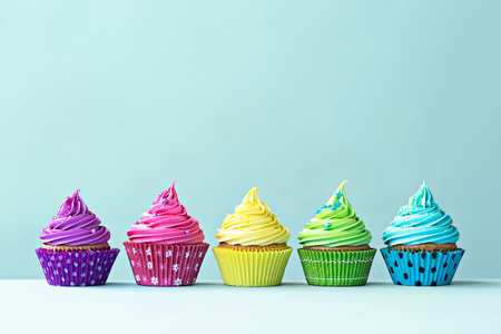 Row of colorful cupcakes on blue Stock Photo