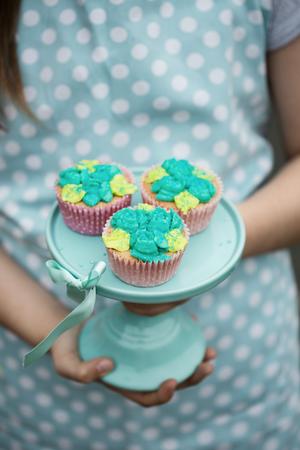 청록색 케이크 서에 서리로 덥은 컵 케이크
