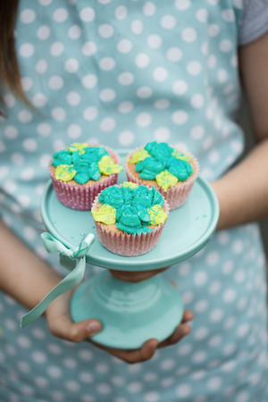Frosted cupcakes on a turquoise cake stand Stock Photo