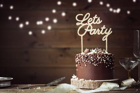 パーティーの設定でチョコレートのお祝いケーキ 写真素材