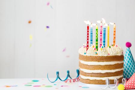 Torta di compleanno con candele colorate a una festa di compleanno Archivio Fotografico - 85478293