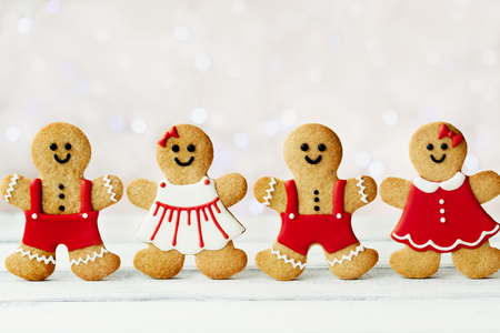 Row of gingerbread men against a background of Christmas lights Stock Photo