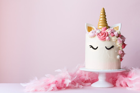Unicorn cake with pink frosting and copy space to side Foto de archivo