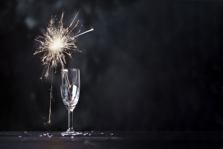 Champagne glass with lit sparkler against a dark background Banque d'images