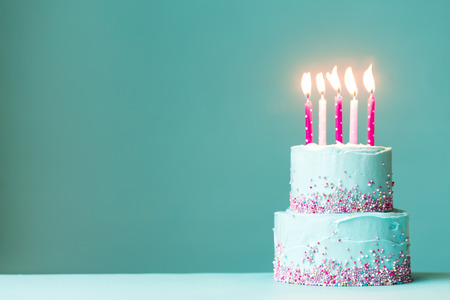 Tiered birthday cake with pink candles and sprinkles Foto de archivo
