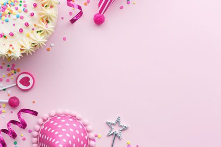 Pink birthday party background with birthday cake and party hats