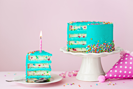 Colorful birthday cake with one slice and a candle