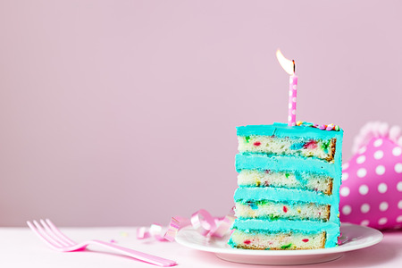Colorful slice of birthday cake with one candle Banco de Imagens