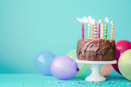 Chocolade verjaardagstaart met kleurrijke kaarsen en ballonnen Stockfoto